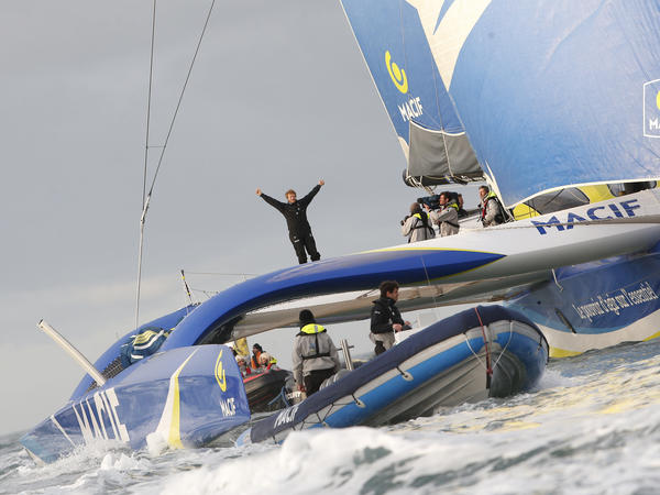 French skipper, François Gabart, waves aboard his 100-foot trimaran as he celebrates his world record off Brest harbor, western France, on Sunday.