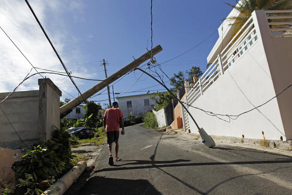 A man walks under a downed light post in Vieques, Puerto Rico.