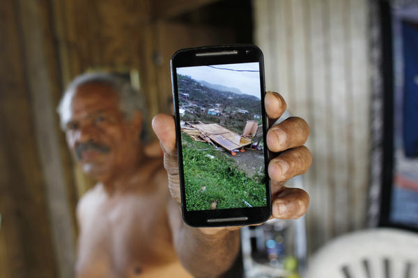 José Ramón Sierra Meléndez, 70, shows a photo of his destroyed house after Hurricane Maria.