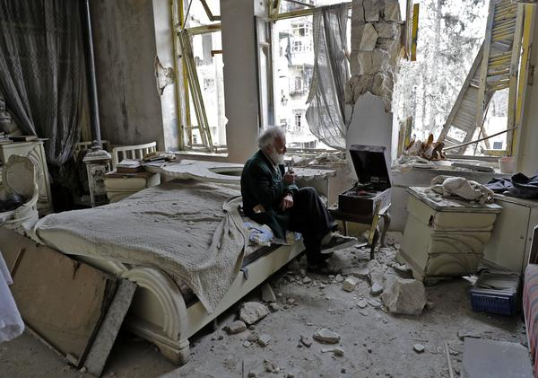 Mohammed Mohiedin Anis, known as Abu Omar, 70, sits amid the rubble in his bedroom while listening to music on his gramophone in the formerly rebel-held al-Shaar neighborhood of Aleppo, Syria.
