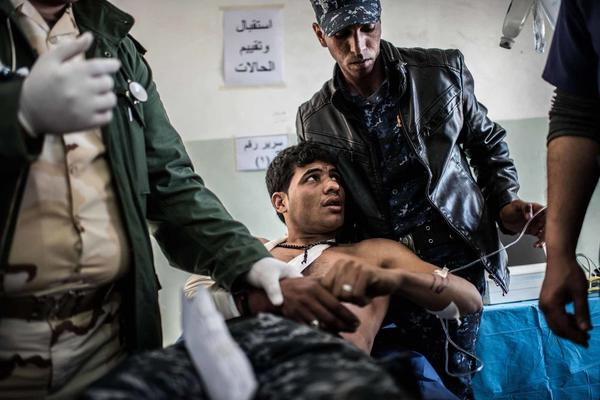 An Iraqi federal police officer wounded by shrapnel while fighting ISIS in west Mosul receives emergency treatment at a trauma center behind the front line.