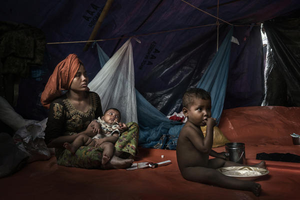 Recently arrived Rohingya refugees eat in shelters in an informal settlement near Kutupalong, Bangladesh, on Sept. 9.