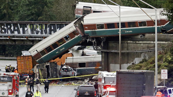 Cars from an Amtrak train lay spilled onto Interstate 5 below and alongside smashed vehicles as some train cars remain on the tracks above on Dec. 18, 2017, in DuPont, Wash. The Amtrak train making the first-ever run along a faster new route hurtled off the overpass Monday near Tacoma.