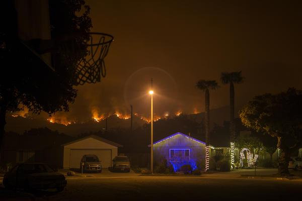 Christmas decorations illuminate a house as the growing Thomas Fire advances toward Santa Barbara County seaside communities.