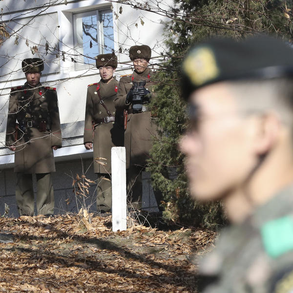 North Korean soldiers look at the South side as a South Korean stands guard near the spot where a North Korean soldier crossed the border on Nov. 13 at the Panmunjom, in the Demilitarized Zone, South Korea.