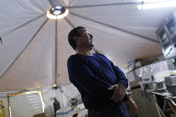 Dr. Jose Carrasquillo works in the clinic run out of military-style tents, which does not have the equipment that would be standard in most hospitals.