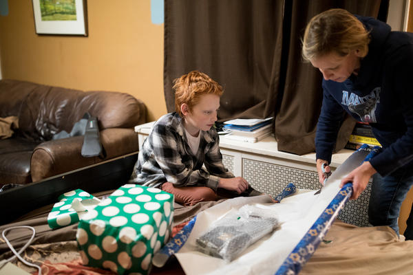 Liam and his mother Heather Leupker wrap gifts. Liam decided to get brain surgery to treat dystonia after his father had the procedure.