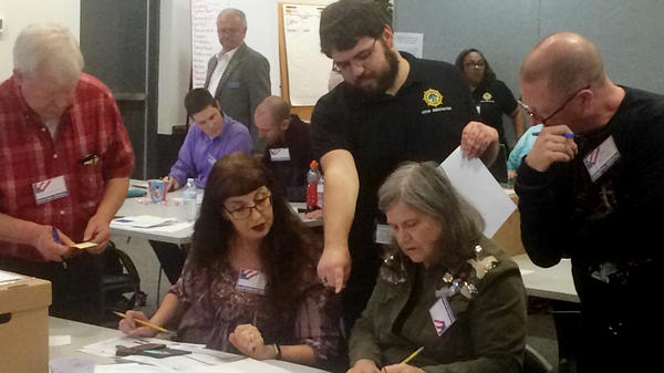 The result of the race between Republican incumbent David Yancey and Democratic challenger Shelly Simonds is still in doubt. Here, election officials in Newport News, Va., examine ballots that a computer failed to scan during a Dec. 19 recount for their House of Delegates race.