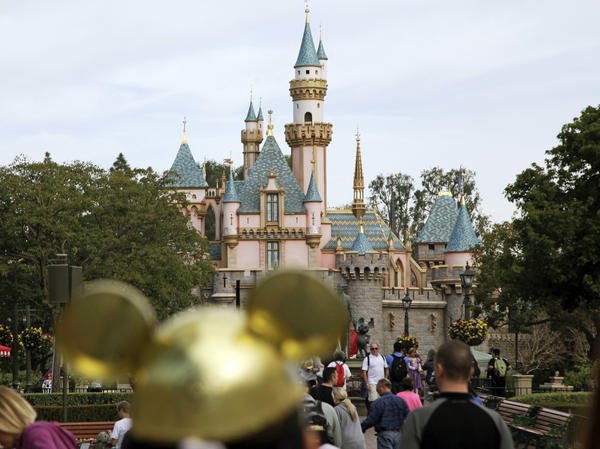 Visitors walk toward Sleeping Beauty's Castle at Disneyland  in Anaheim, Calif. A power outage Wednesday hit parts of the theme park and stopped some rides.