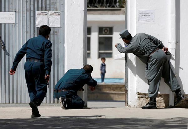 Afghan police gesture to four-year-old Ali Ahmad on Aug. 25 after a suicide attack on a Shiite mosque in Kabul.
