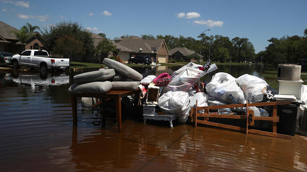 Damaged furniture and personal belongings sit in front of a flooded home in September in Richwood, Texas. Several months after Hurricane Harvey hit southern Texas, residents are still navigating the long recovery process.