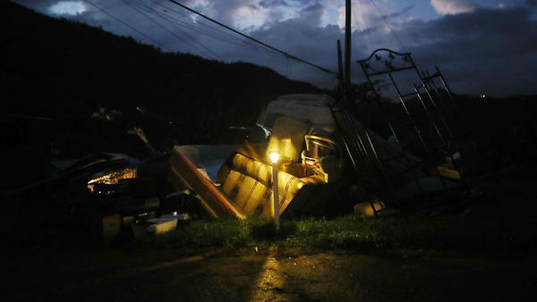 A donated solar lamp in a driveway illuminates storm debris still waiting to be collected earlier this week in Morovis, Puerto Rico.