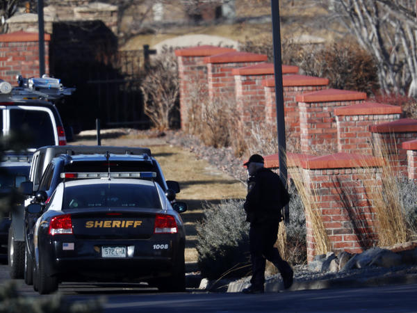 An investigator heads to the scene of shooting Sunday,  in Highlands Ranch, Colo. Authorities in Colorado say one deputy has died and multiple others were wounded, along with two civilians, in a shooting that followed a domestic disturbance in suburban Denver.