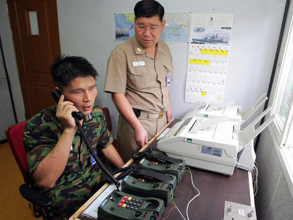 South Korean Lt. Choi Don-rim (left) communicates via a hotline with a North Korean officer at a military office near the Demilitarized Zone in 2005. Pyongyang has announced that it would re-establish a long-closed border hotline.