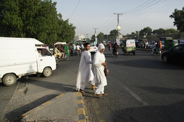 Transgender women walk toward traffic to beg motorists for cash in Lahore. Many believe transgender women have the power to bless and curse humans — a residual belief from when they were seen as sacred.