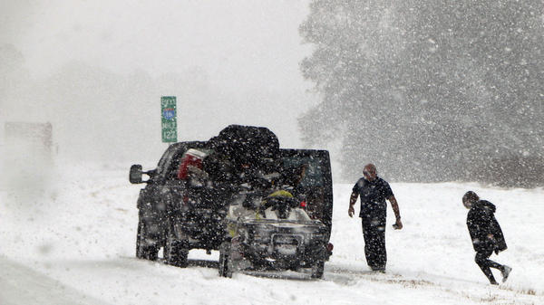 People attend to their vehicle on Interstate 16, near Savannah, Ga., which had the most snow it had seen in 28 years.