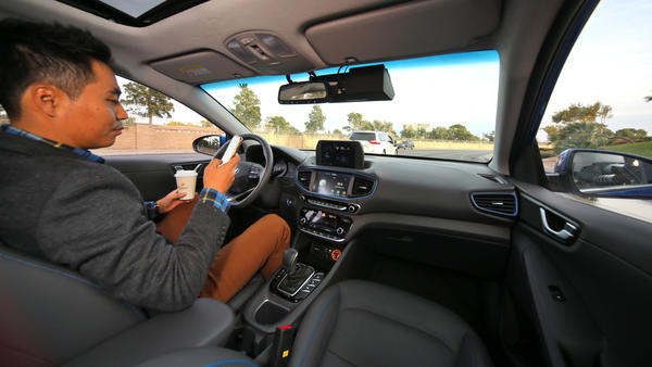 An image released by Hyundai shows a hands-off driver checking his phone and drinking coffee. The company is partnering with Aurora, a U.S. startup, to boost its autonomous vehicle program.