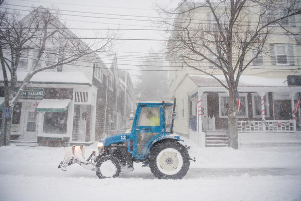 A plow clears snow in Bellport, N.Y., as a winter storm hits the Northeast on Thursday.