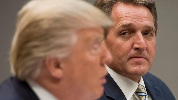 President Trump speaks during a lunch meeting with Republican members of the Senate as Sen. Jeff Flake, R-Ariz., looks on.