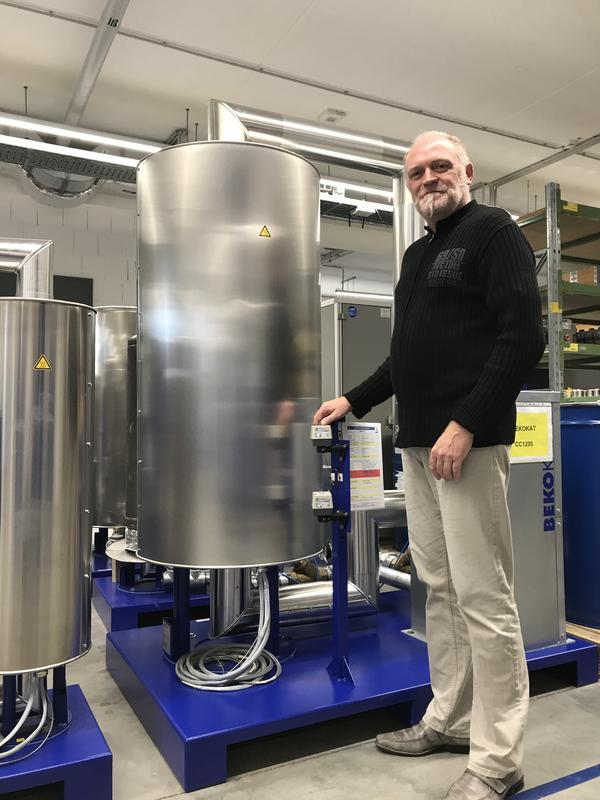 Rainer Stutzel of Beko Technologies stands beside a catalytic converter that cleans compressed air systems. The company exports its products around the world.