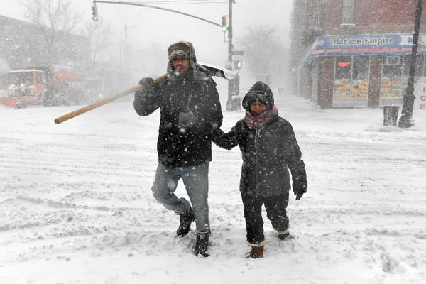 Pedestrians cross the street in Harlem during a snowstorm. As a major winter storm moves up the Northeast corridor, New York City is under a winter storm warning.