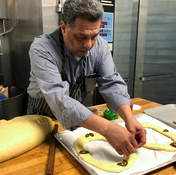 Carlos Benitez, owner of La Mexicana Bakery and Taqueria outside Washington, D.C., puts decorations on <em>rosca de reyes</em> before it goes into the oven. This year Benitez expects to sell almost 300 of the cakes.
