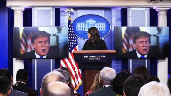 President Trump speaks via video monitors to journalists in White House briefing room Thursday.