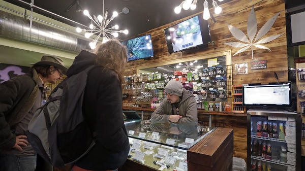 Cannabis consultant Juan Aguilar helps customers shopping for marijuana products Thursday in the Herban Legends pot shop in Seattle.