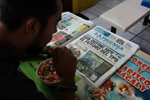"A Salvadoran man reads a newspaper at a market in San Salvador on January 8. The newspaper headline reads: ""The United States will decide today the future of TPS."""