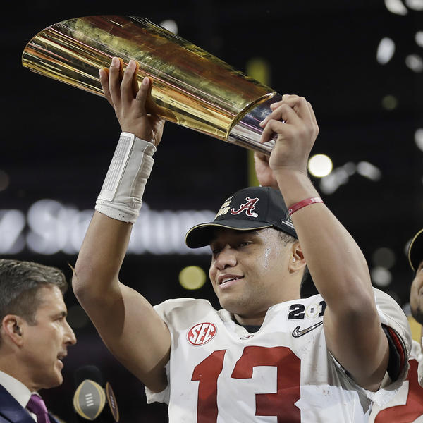 Alabama's Tua Tagovailoa holds up the championship trophy after overtime of the NCAA college football playoff championship game against Georgia, on Monday in Atlanta.