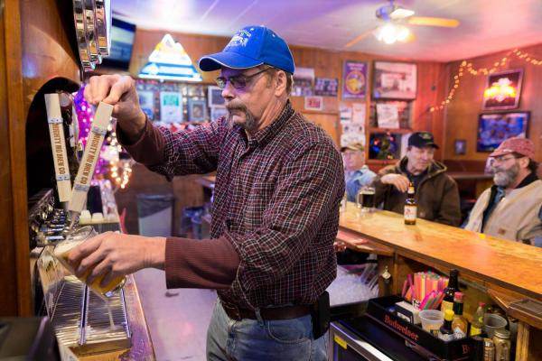 Tracey Somerfeld at Les' Bar drafts a pint of local craft beer. He still farms barley when he's not helping his son run the bar. (Courtesy Food & Environment Reporting Network/Tony Bynum)