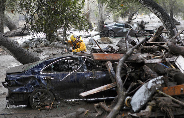 A member of the Long Beach Search and Rescue team looks for survivors in a car in Montecito.
