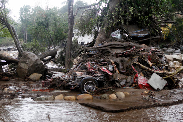 A car and debris smashed against a tree along Hot Springs Road in Montecito, Calif. At least 15 people have died as a result of the mudslides.