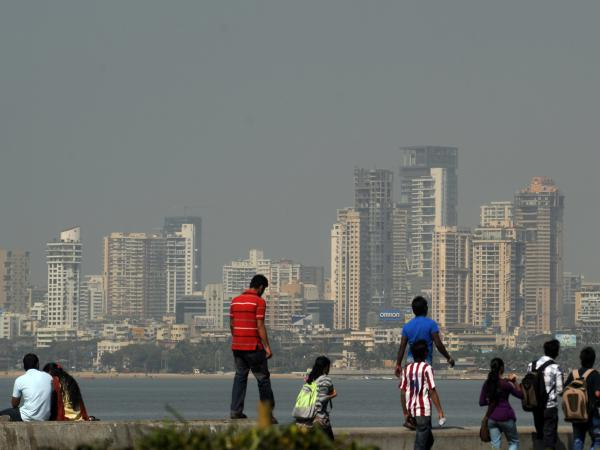The Mumbai city skyline is seen in the background as pedestrians walk and gather on the seaside promenade in Mumbai on January 12, 2012