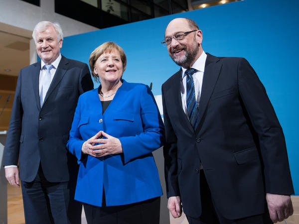 German Chancellor Angela Merkel, head of the Christian Democratic Union, smiles for the media between Horst Seehofer of the Christian Social Union (left) and Martin Schulz of the Social Democratic Party. The three emerged Friday from all-night preliminary coalition talks in Berlin saying they had reached a preliminary deal.