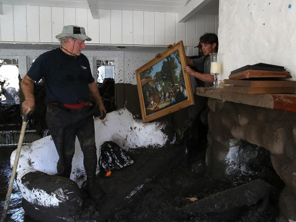 David Drenic (left) and Robert Drenic look for salvageable items in a the home of a family member that was destroyed by a mudslide on Thursday, in Montecito, Calif.