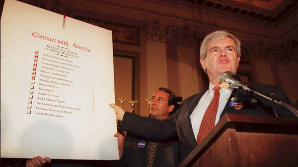 "Newt Gingrich, then speaker of the House in 1994, holds up a copy of the Republican Party's ""Contract with America."""