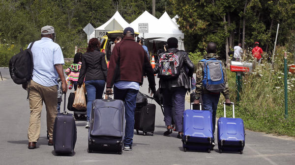 A family from Haiti approach a tent in Saint-Bernard-de-Lacolle, Quebec, stationed by Royal Canadian Mounted Police, as they haul their luggage down Roxham Road in Champlain, N.Y., last August.