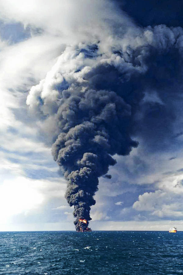 Fires from the Iranian oil tanker darken the skies above the East China Sea on Sunday.
