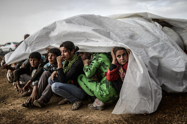 Syrian Kurds take cover from the rain after crossing the border between Syria and Turkey.