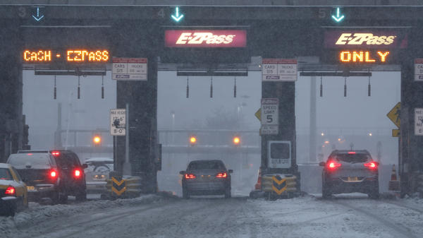 Vehicles are seen at the toll bridge of the Holland Tunnel as snow covers the road during a snowstorm on Feb. 9, 2017, in Jersey City, N.J. More states are turning to tolls as a way to fund long-standing transportation needs.