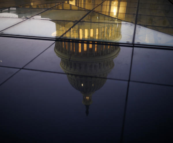 The U.S. Capitol is seen reflected in the windows of the Capitol Visitors Center as lawmakers worked to avert a government shutdown on Friday in Washington, D.C.
