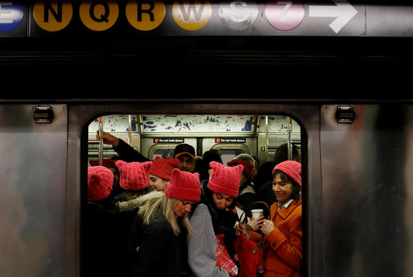 "A group of people wearing ""pussyhats"" board the subway at 42nd Street as they head toward the Women's March in Manhattan."