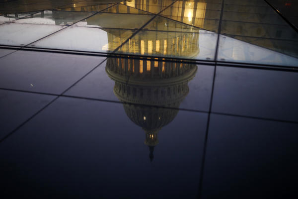 The U.S. Capitol is seen reflected in the windows of the Capitol Visitors Center as lawmakers debated ahead of the government shutdown on Jan. 19.