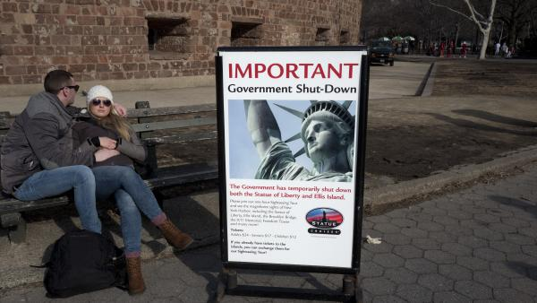 Tourists rest on a bench on Sunday in lower Manhattan after discovering that the Statue of Liberty is closed due to the government shutdown. It's reopening today using state funding.
