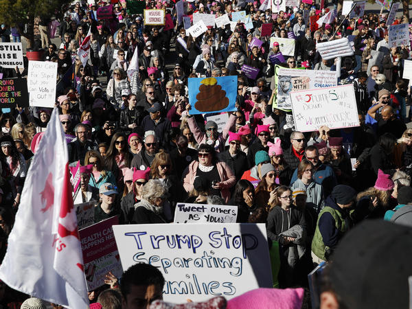 People wave flags and hold signs while entering the Women's March rally, Sunday, in Las Vegas.
