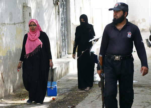 A Pakistani policeman guards a team of polio vaccinators during an immunization drive in Karachi on January 22. Officials have stepped up protection in the wake of the January 18 attack.