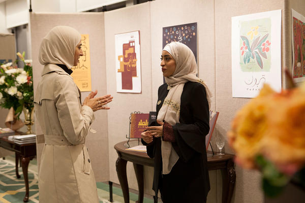 "Rawabi al-Sanusi, 23, (right) speaks with another artist at the exhibition at the Saudi embassy. ""I always liked to draw,"" she says. ""I was like the weird one in my family."" She designed a hardcover book paying tribute to generations past, ""to show the diversity of Saudi Arabian families,"" she says. Her great-great-grandfather, she says, ""was a king of Libya for a short time."""