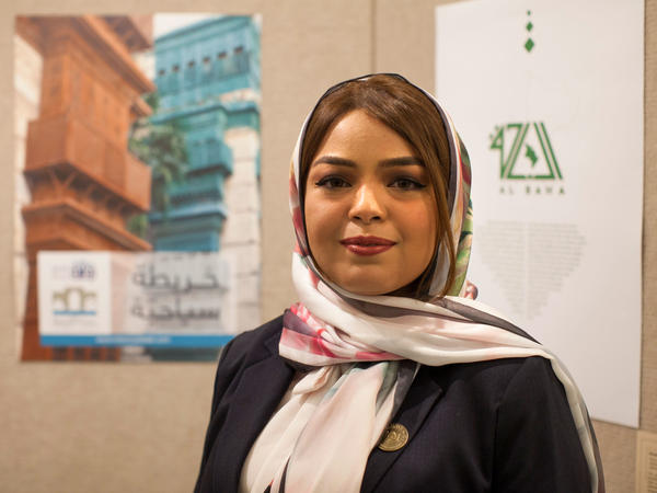 Rana Fatami stands in front of a poster for her Historical Jeddah app.