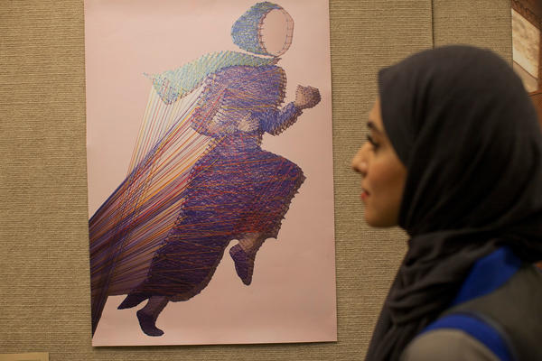 "Bashayer Alkhayyat, the designer of a running abaya, stands in front of a poster showing a life-size, interactive installation she created depicting a woman running in an abaya and hijab. Viewers are encouraged to cut the colored threads, which she says represent ""limitations from fitness."""